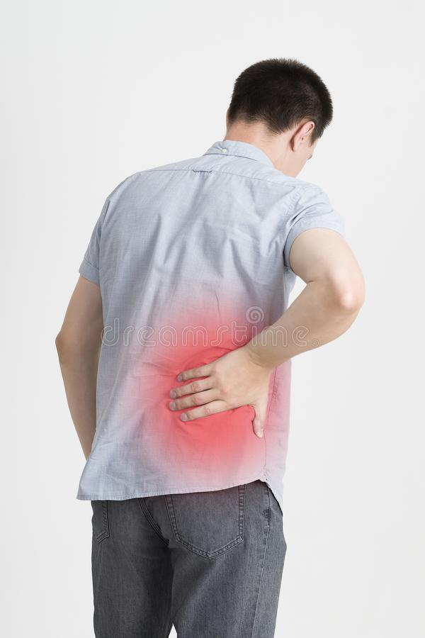 Back pain, kidney inflammation, ache in man`s body. On gray background with red dot stock photography