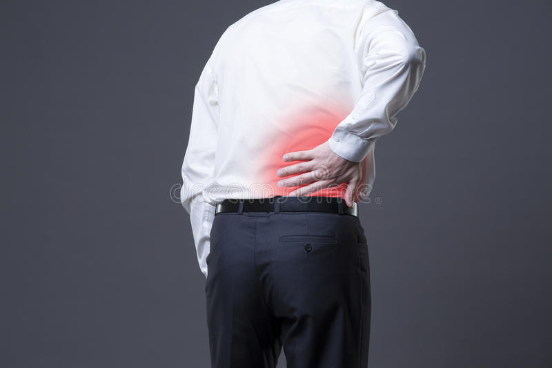 Back pain, kidney inflammation, ache in man`s body. On gray background with red dot royalty free stock photos