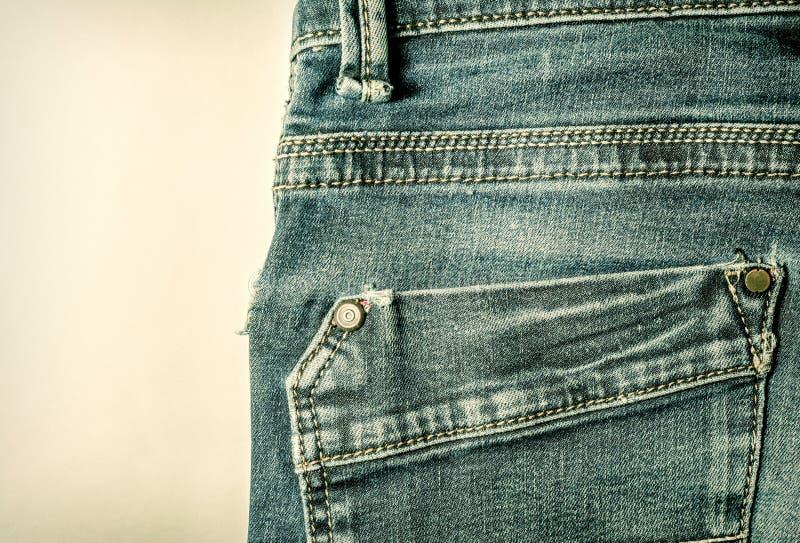 Back pocket stitching blue jeans vintage style close-up. On vintage background royalty free stock image