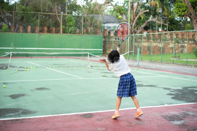 Back portrait of Asian girl playing tennis at old outdoor tennis royalty free stock photo