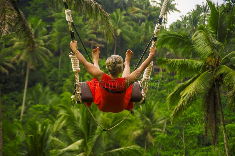 Back portrait of attractive happy middle aged woman with grey hair riding rainforest swing carefree swinging and enjoying. Outdoors lifestyle back portrait of stock photography