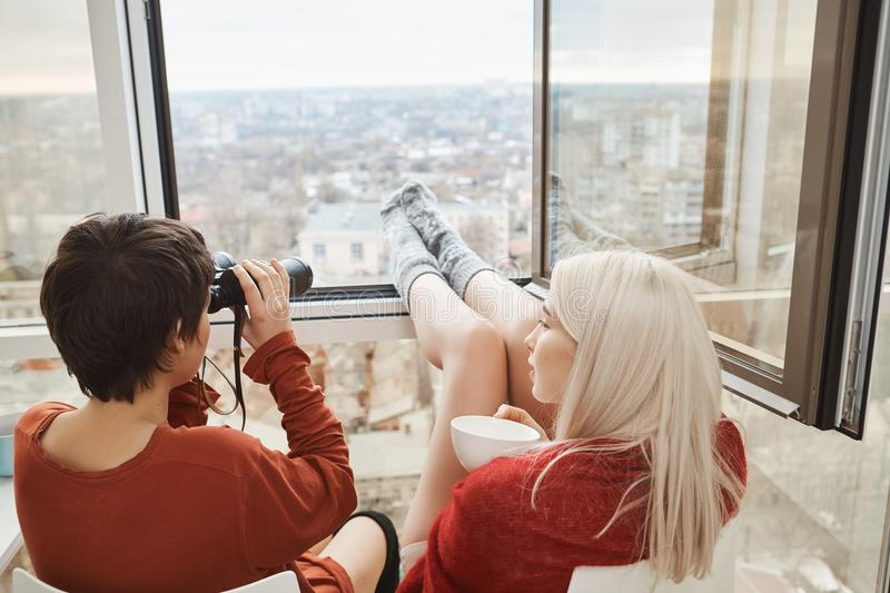 Back portrait of hot attractive women sitting on balcony with legs leaned on window, using binocular and drinking coffee royalty free stock image
