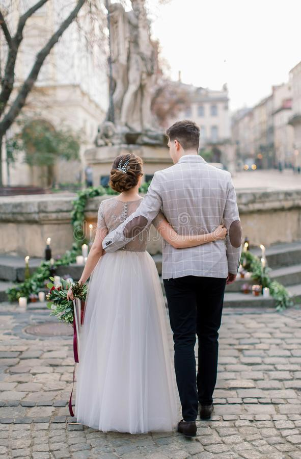 Back portrait of stylish couple bride and groom, embracing, standing in the front of wedding decor on monument stairs in stock image