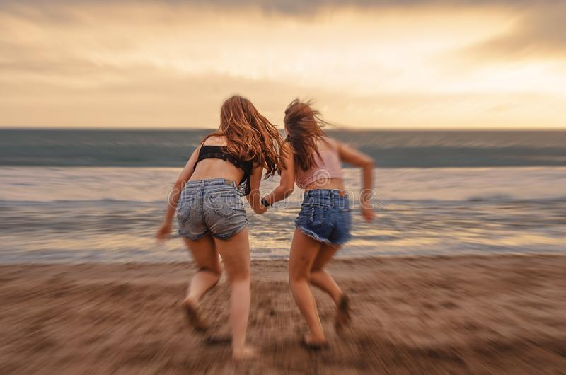 Back portrait of two happy and attractive young women girlfriends holding hands on the beach running to the sea under beautiful su stock photo