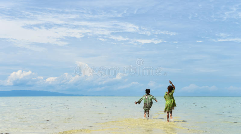Back portrait of two native young sisters running and jumping in the shallow water on tropical beach. stock photo