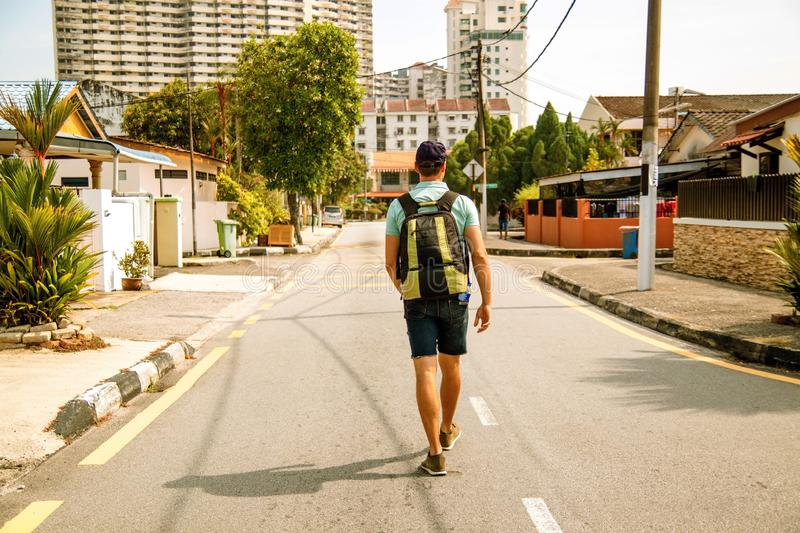 Back portrait of Young man traveler with backpack travel concept . Happy young guy with backpack travels in asian city on sunny day royalty free stock images