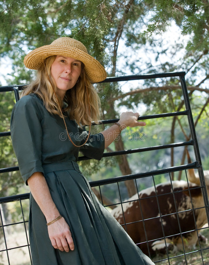 Back at the Ranch. Pretty 40s-ish woman in straw hat and retro dress at ranch gate stock image
