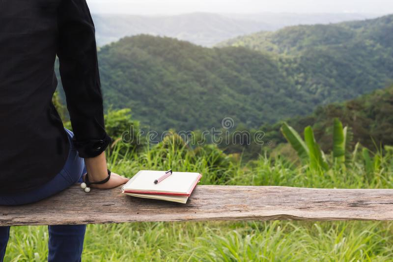 Back of rare view women sit on wood bench with black or empty di stock photo