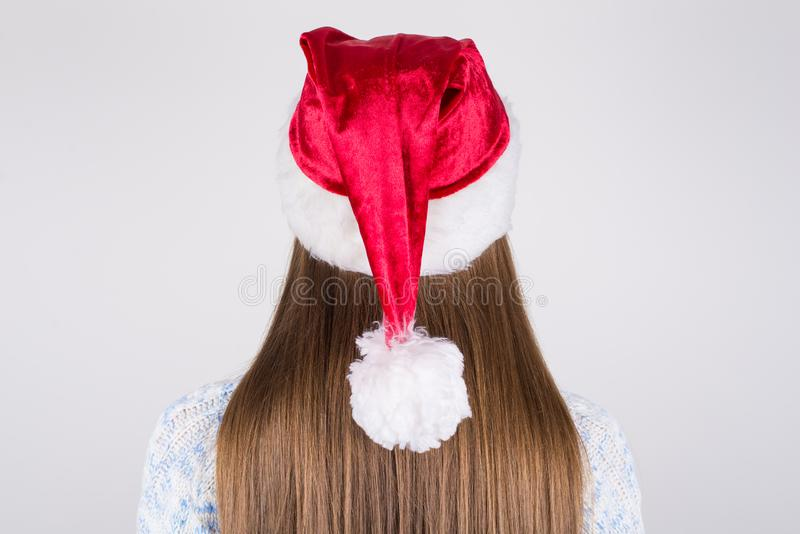 Back rear behind close up photo portrait of charming gorgeous lady having nice straight smooth silky hair wearing santa`s hat on. Head isolated grey background stock images