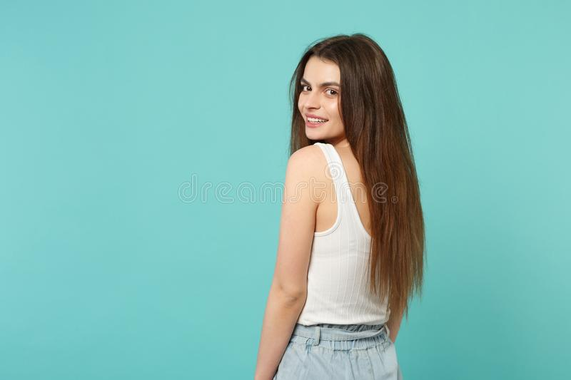 Back rear view of attractive cute young woman in light casual clothes looking back isolated on blue turquoise wall royalty free stock photos