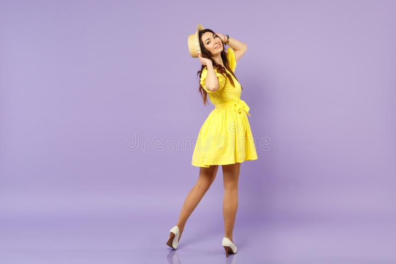 Back rear view of pretty young woman in yellow dress putting hands on summer hat looking back isolated on pastel violet royalty free stock photo