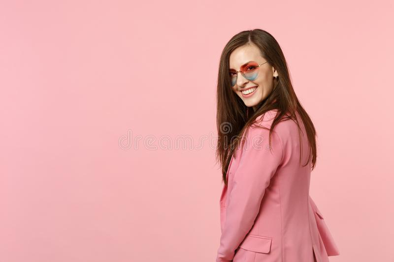 Back rear view of smiling attractive pretty young woman in heart glasses looking back isolated on pastel pink wall royalty free stock image