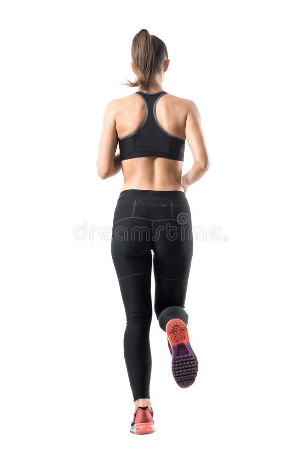 Back rear view of young female jogger in leggings and tank top running. stock photo