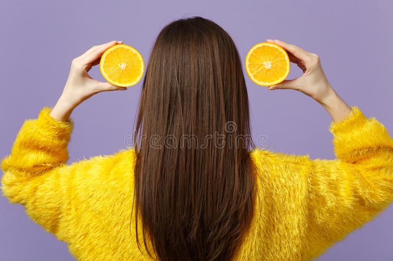Back rear view of young woman in fur sweater holding halfs of fresh ripe orange fruit near hair isolated on violet. Pastel background. People vivid lifestyle stock photos