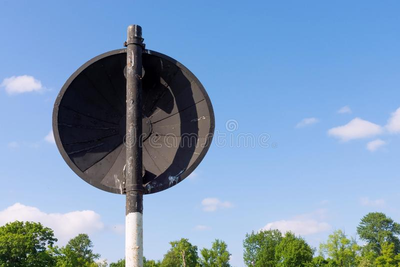 Back or reverse side of an old road sign. The old round road sign is located the back closeup on a rack from a pipe and separately against the sky royalty free stock image