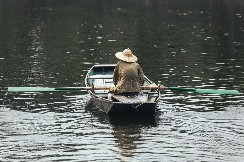 Back of rowing boat man wearing green shirt and conical hat sitting in a boat with paddles over the river in background. royalty free stock image