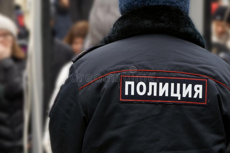 Back of a russian policeman wearing an uniform with an emblem royalty free stock photos