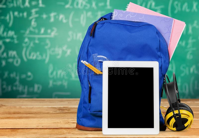Blue School Backpack with tablet and earphones on royalty free stock photo