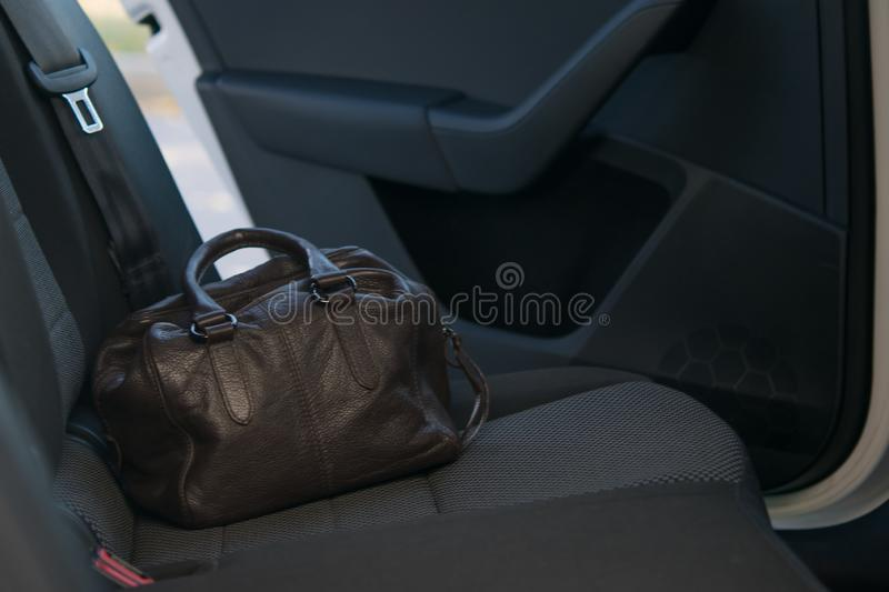 On the back seat of the car is a brown leather bag on the background of the door ajar. forgotten. stock photo