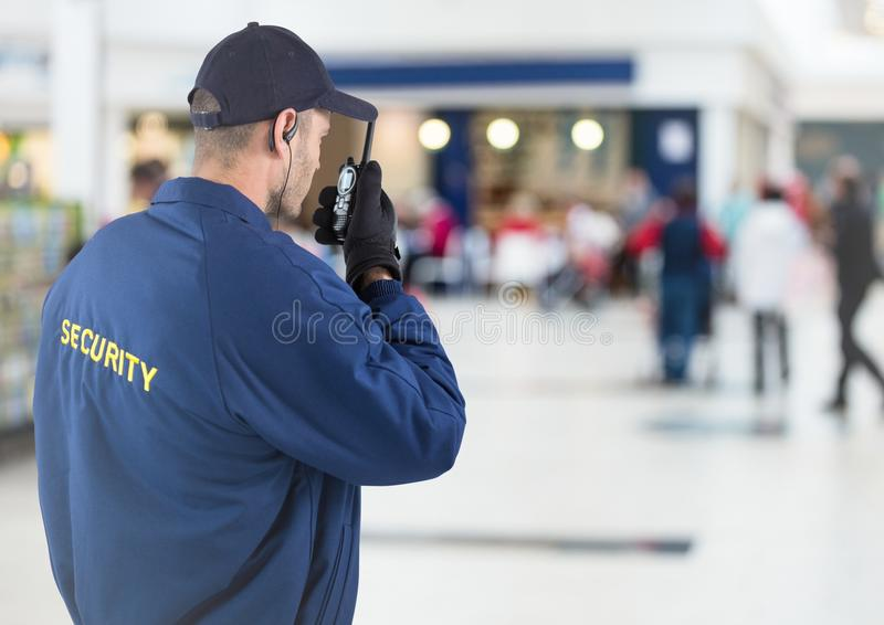 Back of security guard with walkie talkie against blurry shopping centre. Digital composite of Back of security guard with walkie talkie against blurry shopping stock images