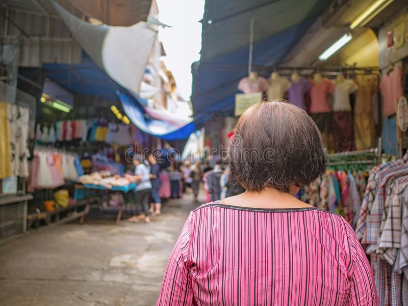 Back of Senior asian women walking and shopping on `Phahurat ` Road the Old marketplace in Bangkok City. Back of Senior asian woman walking and shopping on ` stock photography