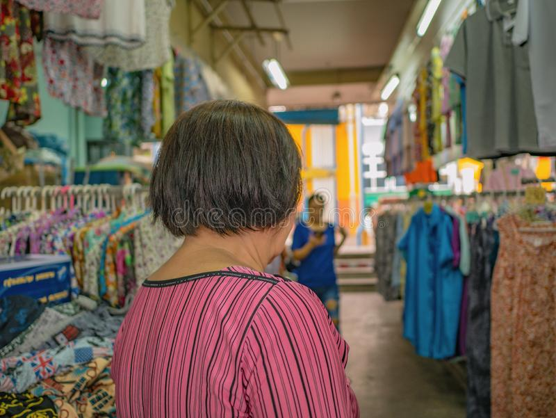 Back of Senior asian women walking and shopping on `Phahurat ` Road the Old marketplace in Bangkok City. Back of Senior asian woman walking and shopping on ` royalty free stock photos