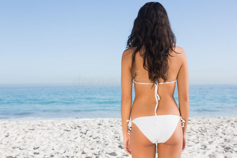 Back of sexy brunette posing in white bikini