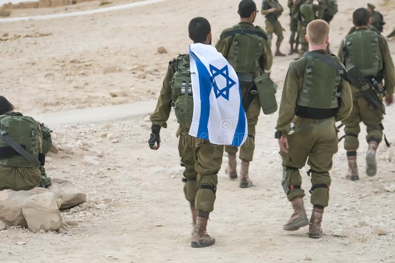 Back shot of several soldiers of israel army walking with israel national flag. Military man bearing israel flag on his shoulder royalty free stock photos