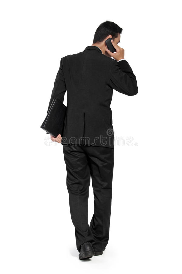 Back shot of walking businessman, talk on phone royalty free stock photography