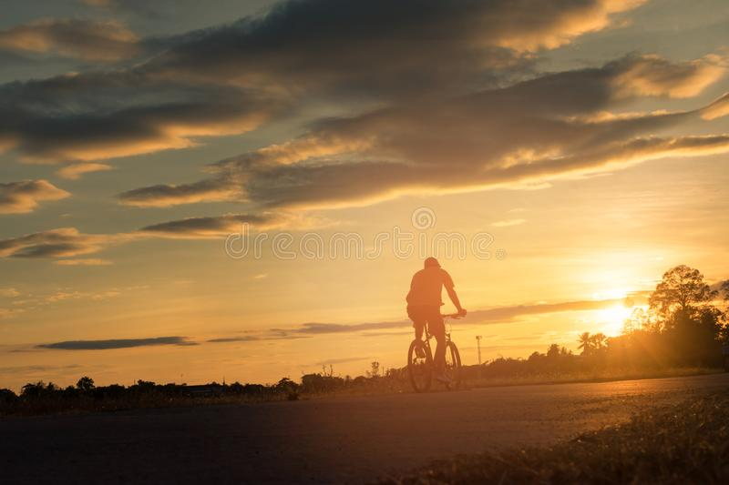 The back side of cyclist rides bicycle on sunset time background. stock photo