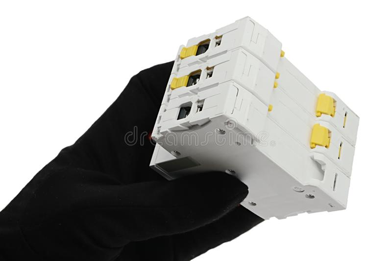 Back side of three-fold modular electrical installation component held in left hand of electrician, white background. royalty free stock photo
