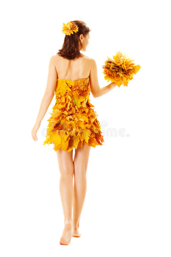 Back side view of Autumn woman in dress of maple leaves. Back side view Autumn woman in fashion dress of maple leaves holding bouquet leaves. Isolated stock image