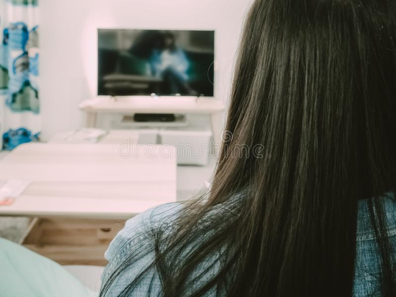 Back side view of black hair woman sit, relax and watch TV in he stock photos