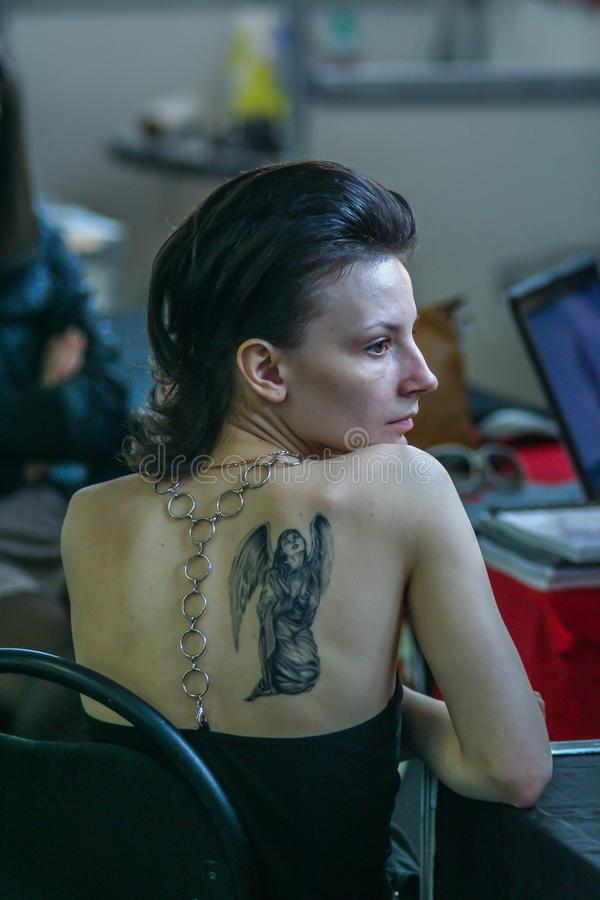Back side view portrait of young woman with tattoo art on the shoulder blade. People and body art. 2010.05.01, Moscow, Russia. Back side view portrait of young royalty free stock photo