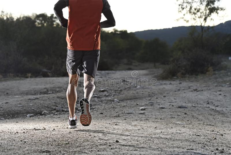 Sport man with ripped athletic and muscular legs running uphill off road in jogging training workout royalty free stock photos