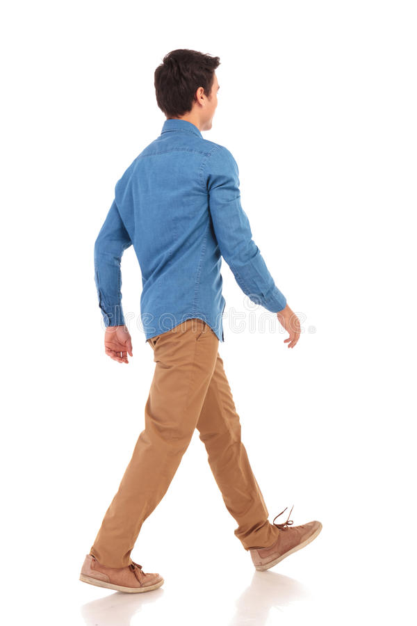 Back side view of a walking young casual man royalty free stock photography