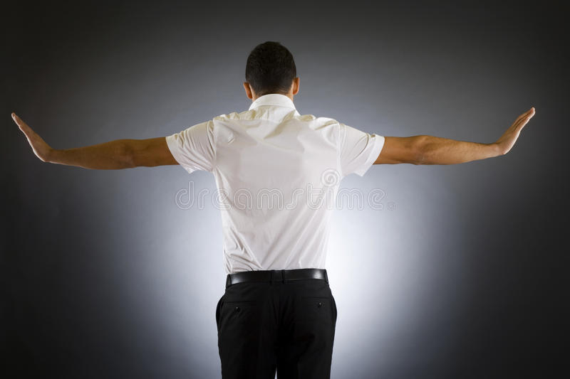 Back side of a well dressed businessman. Stock photo of the back side of a well dressed businessman holding his arms up royalty free stock images