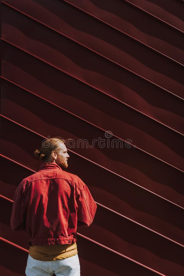 Back side young hipster man on red wall view. Urban lifestyle concept. Waist up back side portrait of young red haired hipster guy staying on red building wall stock image