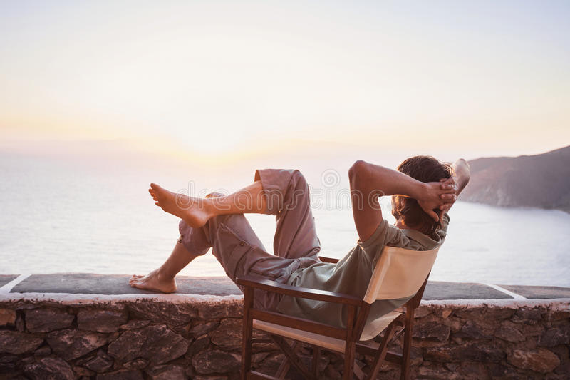 Back side of young man looking at the sea, vacations lifestyle concept stock image