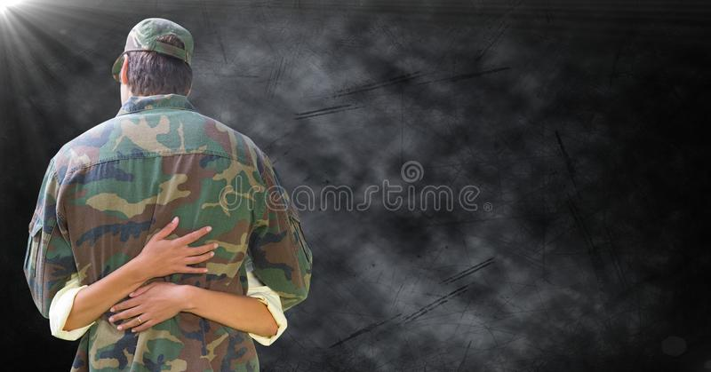 Back of soldier being hugged against black grunge background with flare royalty free stock photo
