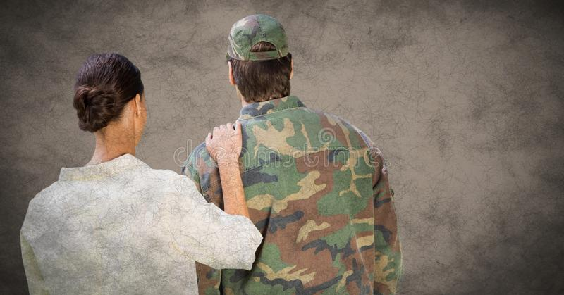 Back of soldier and wife against brown background with grunge overlay stock photo