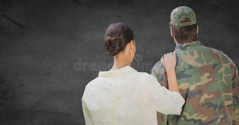 Back of soldier and wife against grey wall with grunge overlay royalty free stock images