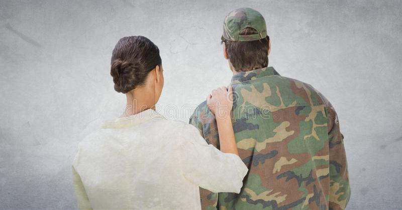Back of soldier and wife against white wall with grunge overlay royalty free stock images