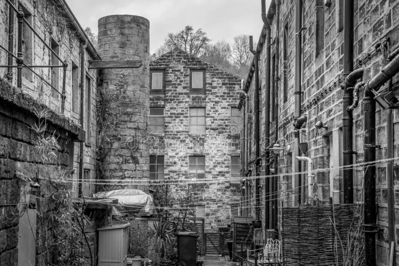 A yard in an industrial northern England town. The back of some terraced houses and the back of a factory and a open courtyard. bins, fencing and a industrial royalty free stock photo
