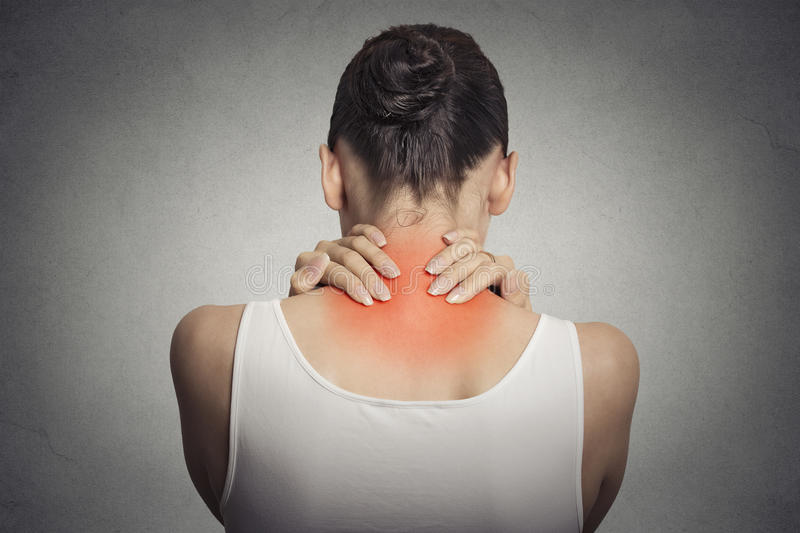 Back spine disease. Closeup view tired female massaging her neck stock photography