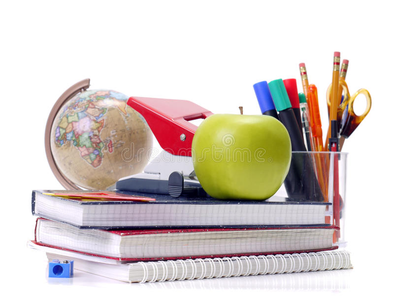 Back to school. Assorted school aids and green apple shot over white background