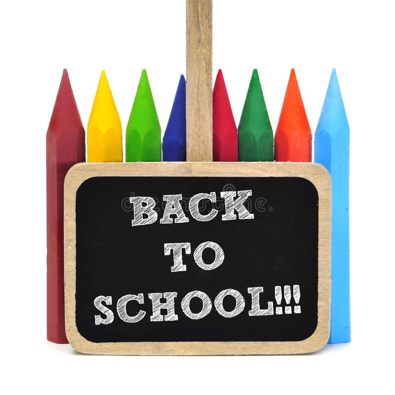Back to school. Sentence back to school written in a blackboard label and some crayons of different colors in the background stock photography