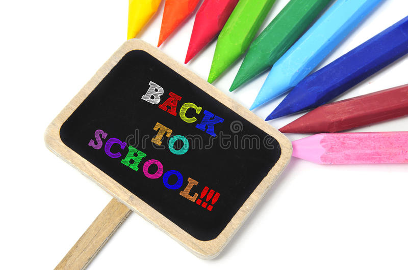 Back to school. Sentence back to school written in a blackboard label and some crayons of different colors in the background royalty free stock image