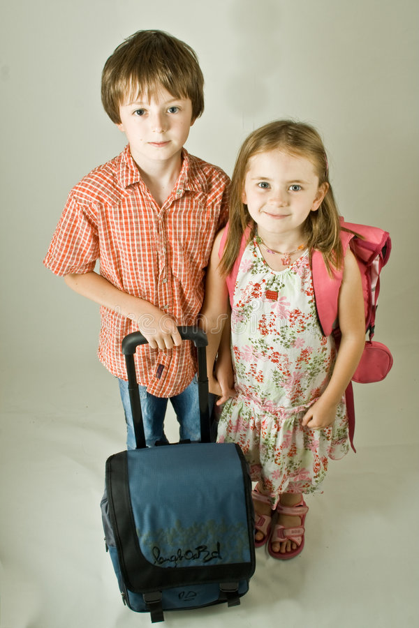 Back to School. Brother and sister, schoolboy and schoolgirl, with school bags, about to go back to school. Full-length vertical portrait isolated against a royalty free stock photos