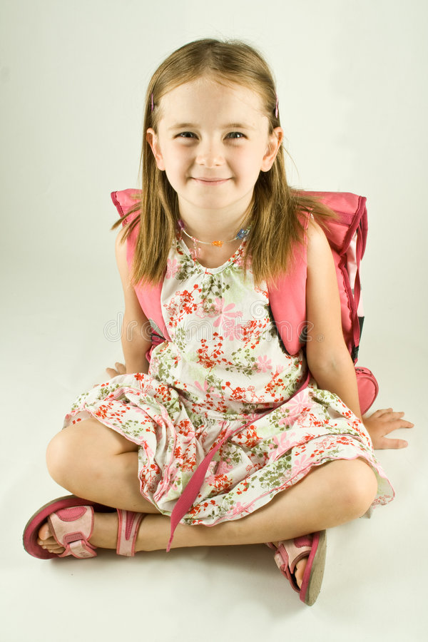 Back to School. Smiling young girl with a print dress, sandals and a school bag on her back, seated in front of a white background, isolated stock image